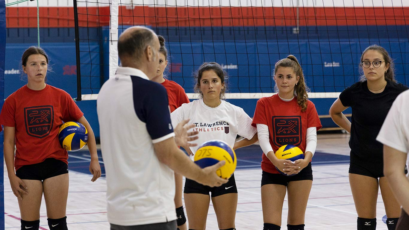 Womens vollyball students listening to a coach's instructions